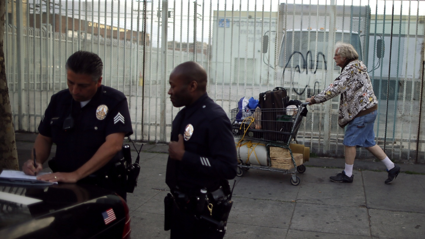 LAPD Sergeant Mark Wright (L) makes notes on downtown Los Angeles' Skid Row,as a homeless man walks by.