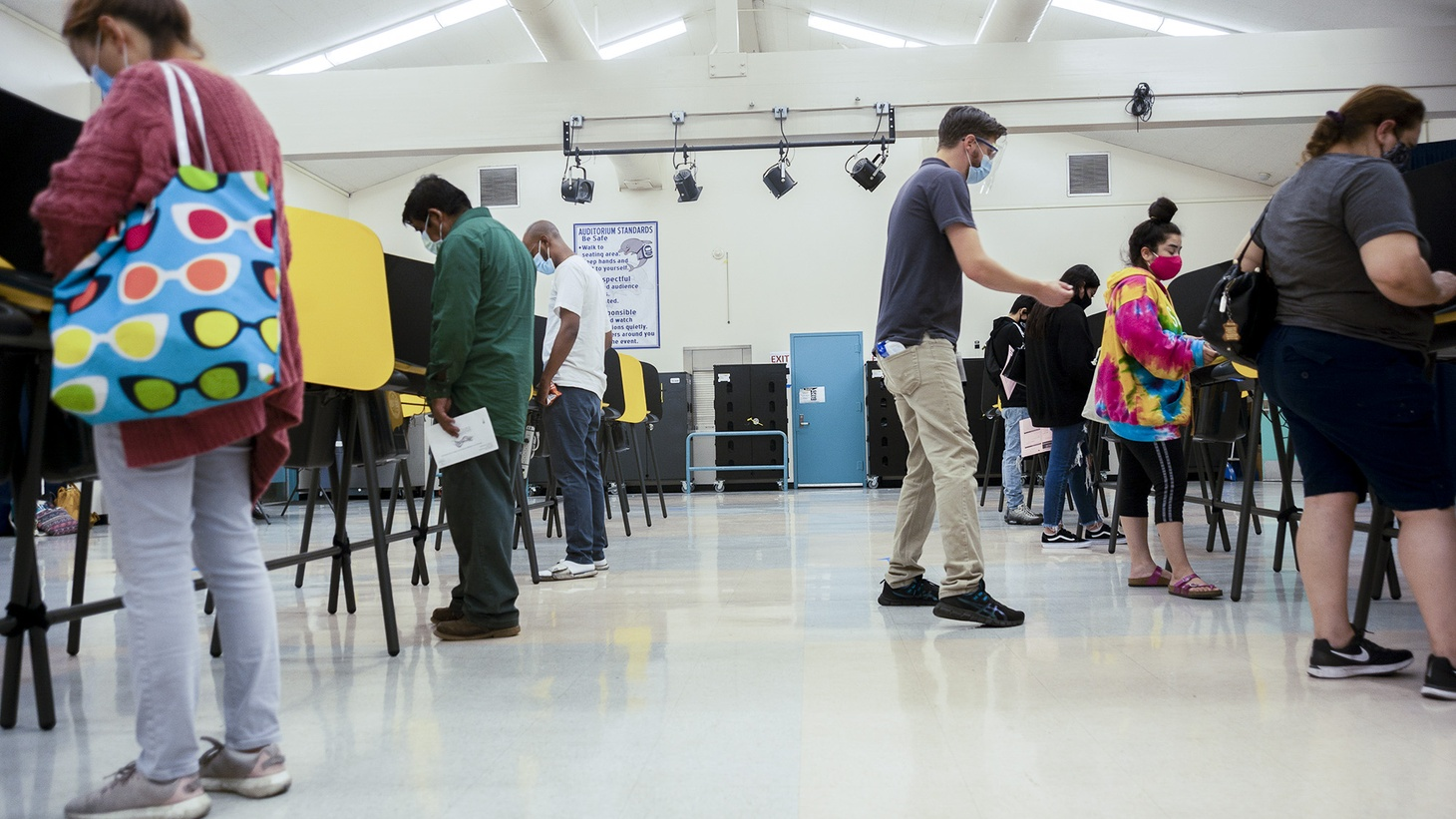 Volunteer poll worker David Saunders helps a voter at a Los Angeles Elementary School polling place on Election Day. Early California results provided some answers but remaining questions.