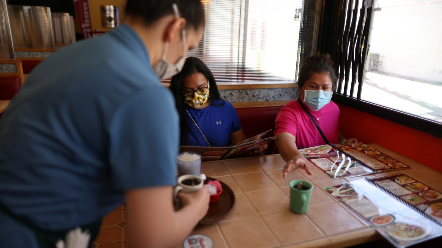 Alexis Reyna, 20 serves coffee to Ana Dominguez, 34, and Saray Aguilar, 33, at Chalio Mexican Restaurant, as the coronavirus (COVID-19) disease continues, in East Los Angeles, California, U.S., May 26, 2021.