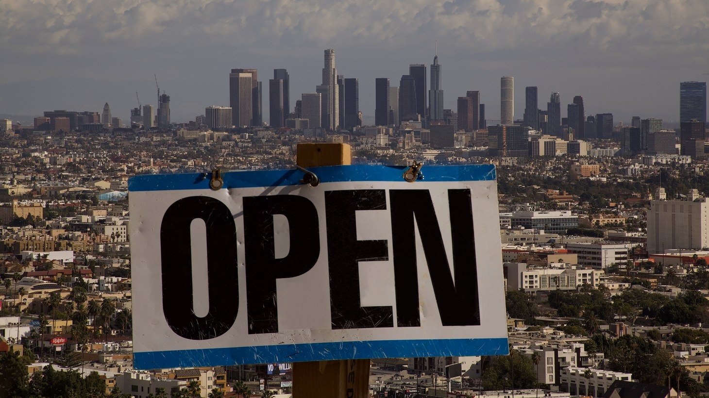 """An """"open"""" sign is seen with downtown Los Angeles in the background."""