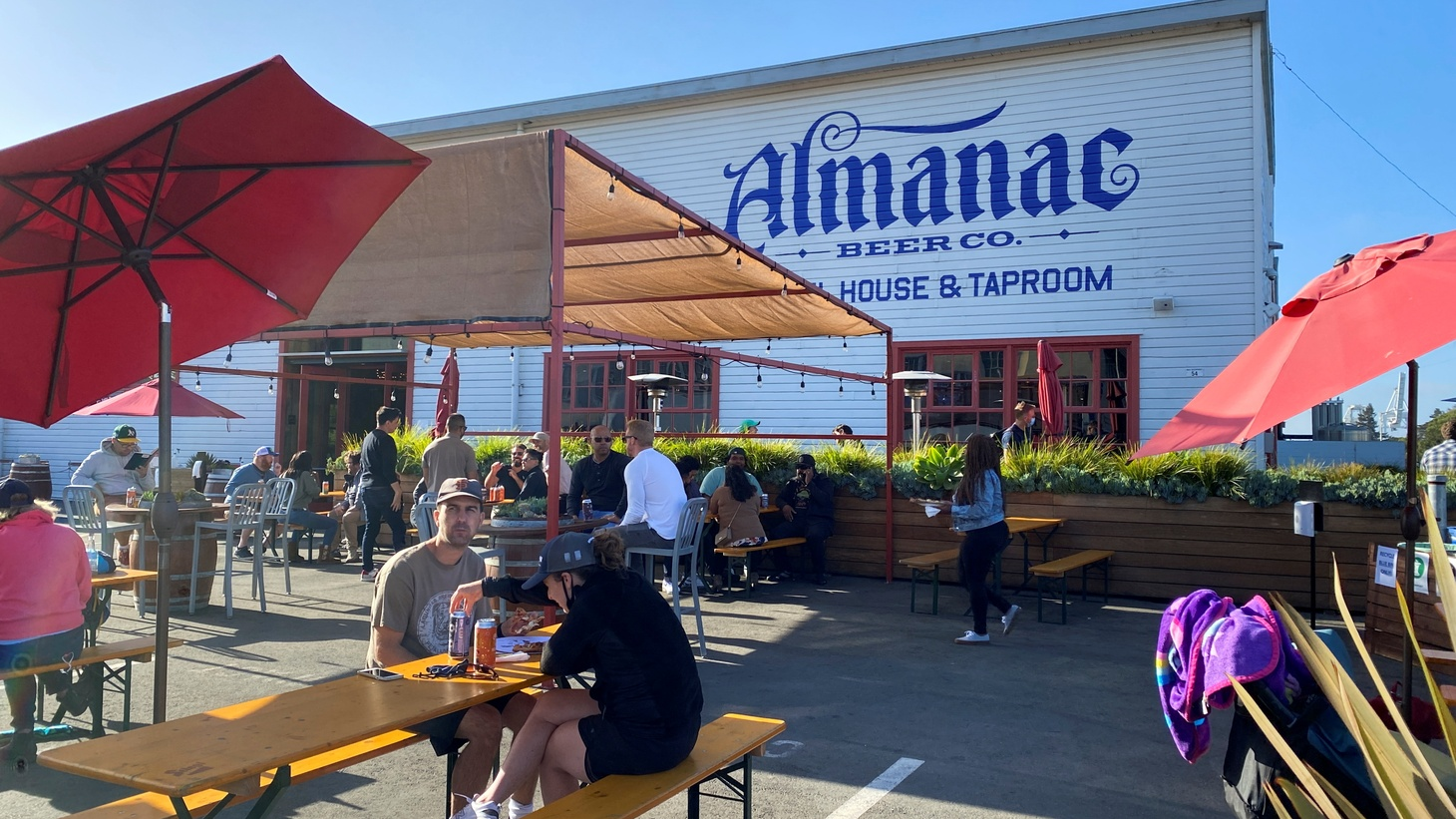 Customers drink, eat and talk at well-spaced tables on Almanac Taproom's former parking lot-turned-pandemic beer garden in Alameda, California, U.S. June 4, 2021