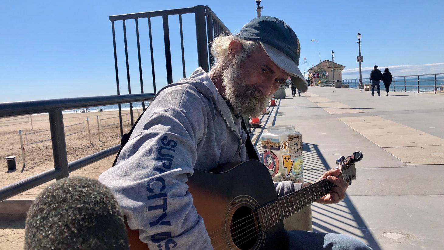 Mike Cartlock, strums his guitar in Huntington Beach.