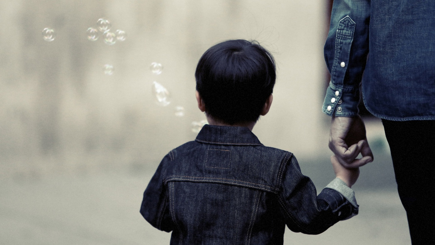 A boy blowing bubbles with his guardian.