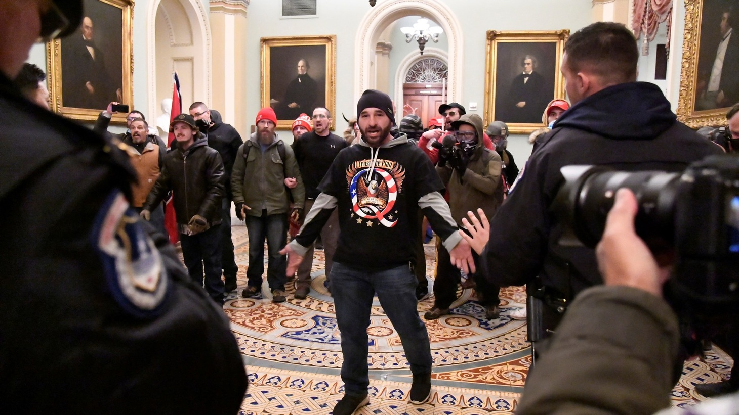 A supporter of President Donald Trump confronts police as extremists demonstrate on the second floor of the U.S. Capitol near the entrance to the Senate after breaching security defenses, in Washington, U.S., January 6, 2021.