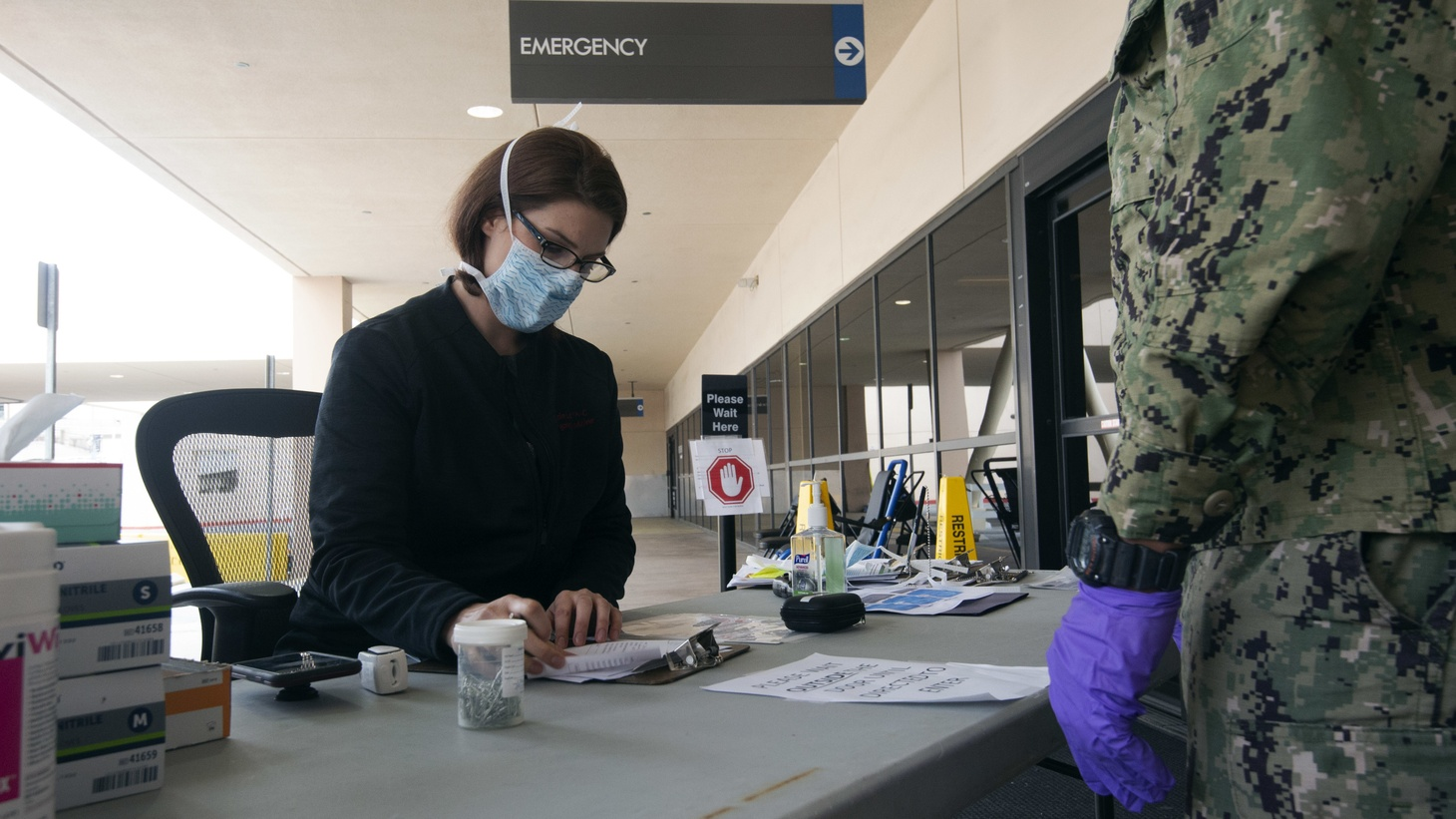 "A woman at a ""Streamer Desk"" at Naval Medical Center San Diego (NMCSD). The desk is the first stop in determining whether or not a patient goes to the screening tent or to normal patient care. March 31, 2020."