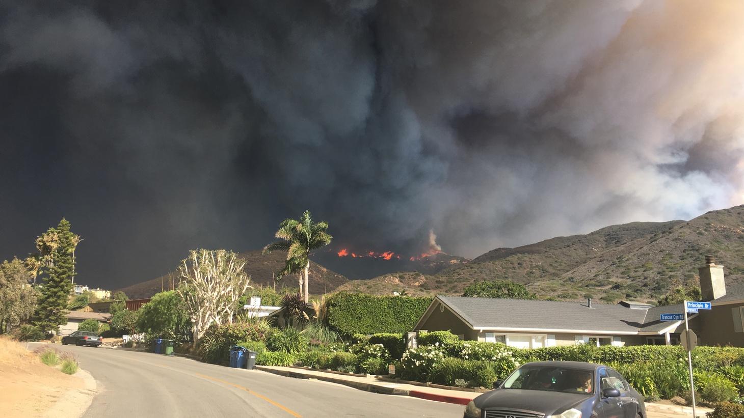 Dark smoke fills the sky as the Woolsey Fire bears down on Malibu.
