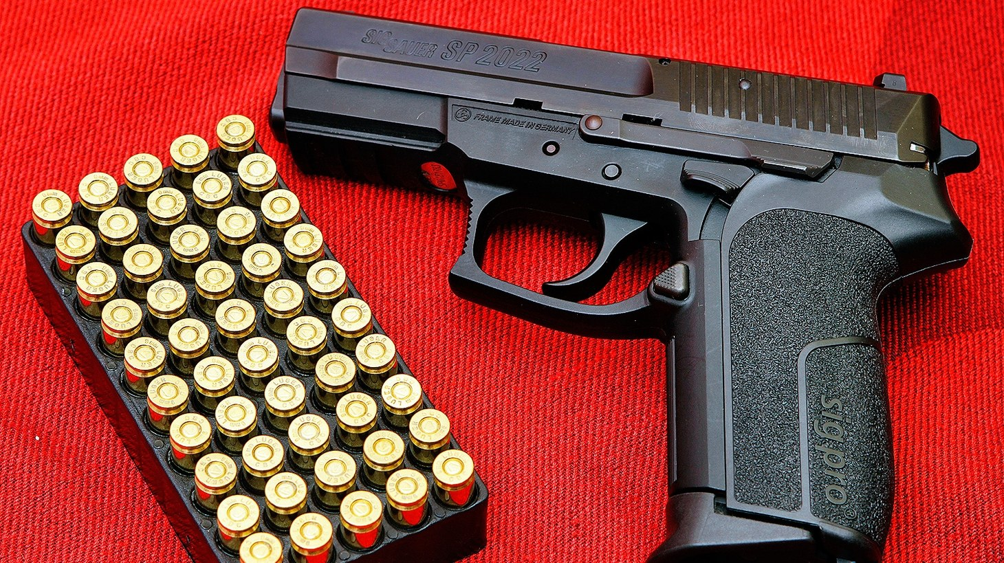 SIG Pro semi-automatic pistol (SP 2022 variant) depicted alongside a box of 9×19 Luger ammunition. UC Davis researchers found that about 110,000 new firearms were purchased statewide through mid-July.