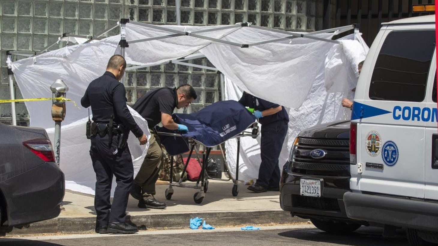 Coroner's officials remove the body of a homeless man found on the sidewalk at Massachusetts Avenue and Sepulveda Boulevard in Los Angeles on Sept. 1, 2019.