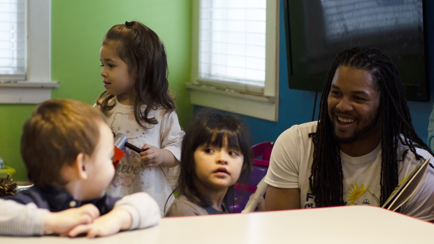 Keenan Davis sits with some of the children at Davis Family Child Care.
