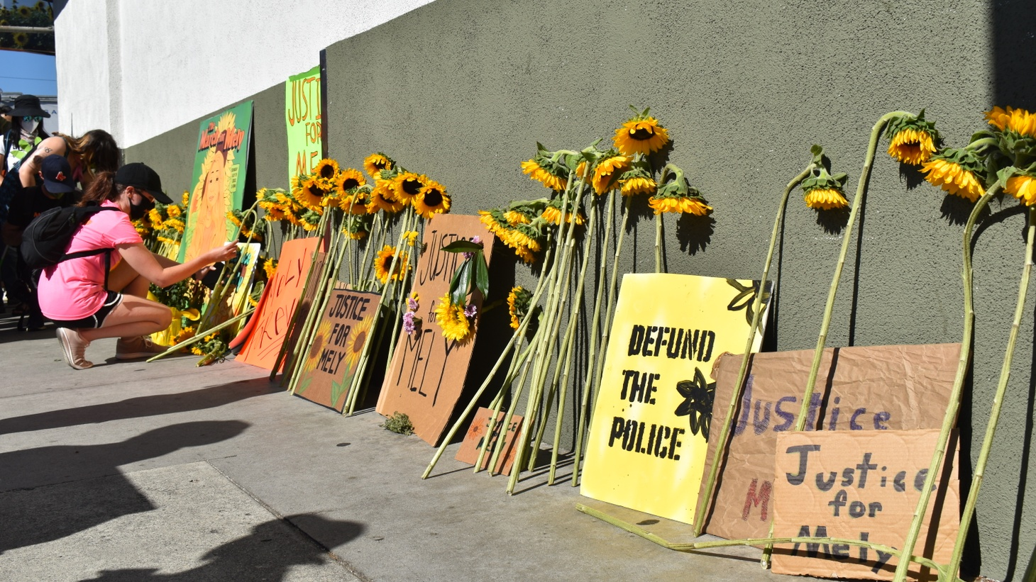 Protesters place their sunflowers on a makeshift memorial on the wall of the Silver Lake Trader Joe's.