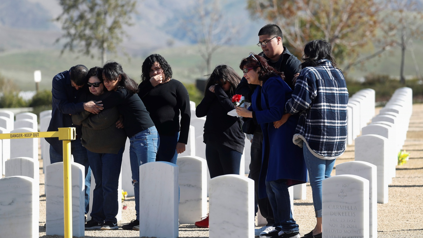 Members of the Gutierrez family mourn graveside, during a non customary military burial service amid an outbreak of COVID-19, for Robert Gutierrez, who was given a Purple Heart award for serving in the Vietnam War and passed away of a non-coronavirus related death, at the Bakersfield National Cemetery in Arvin, California, April 3, 2020.