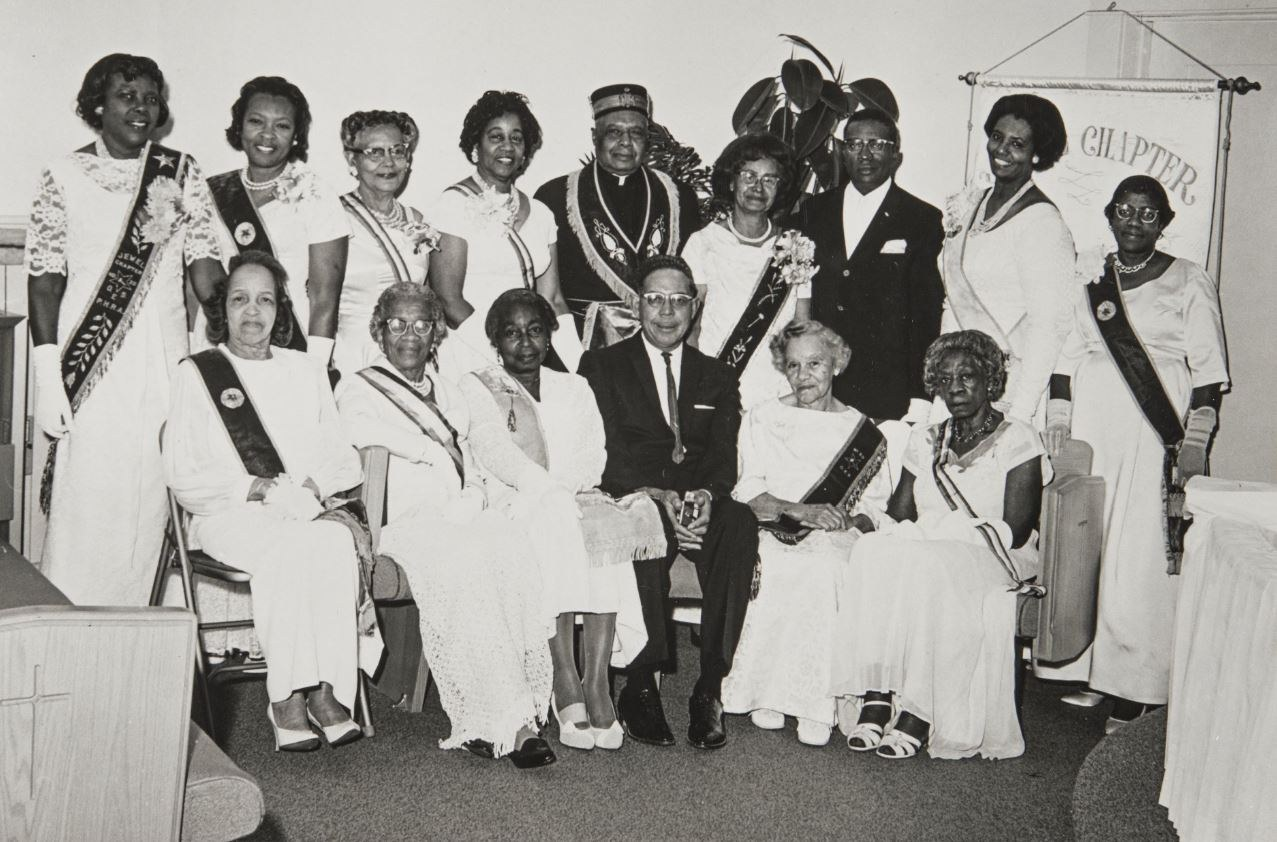 Group portrait of fifteen members of the Santa Barbara Eastern Star Jewel Chapter Number 20. Nine adults stand behind six seated adults. Each of the twelve women wear a sash over her clothing. Image originally obtained from Laura K. Simmons.JPG