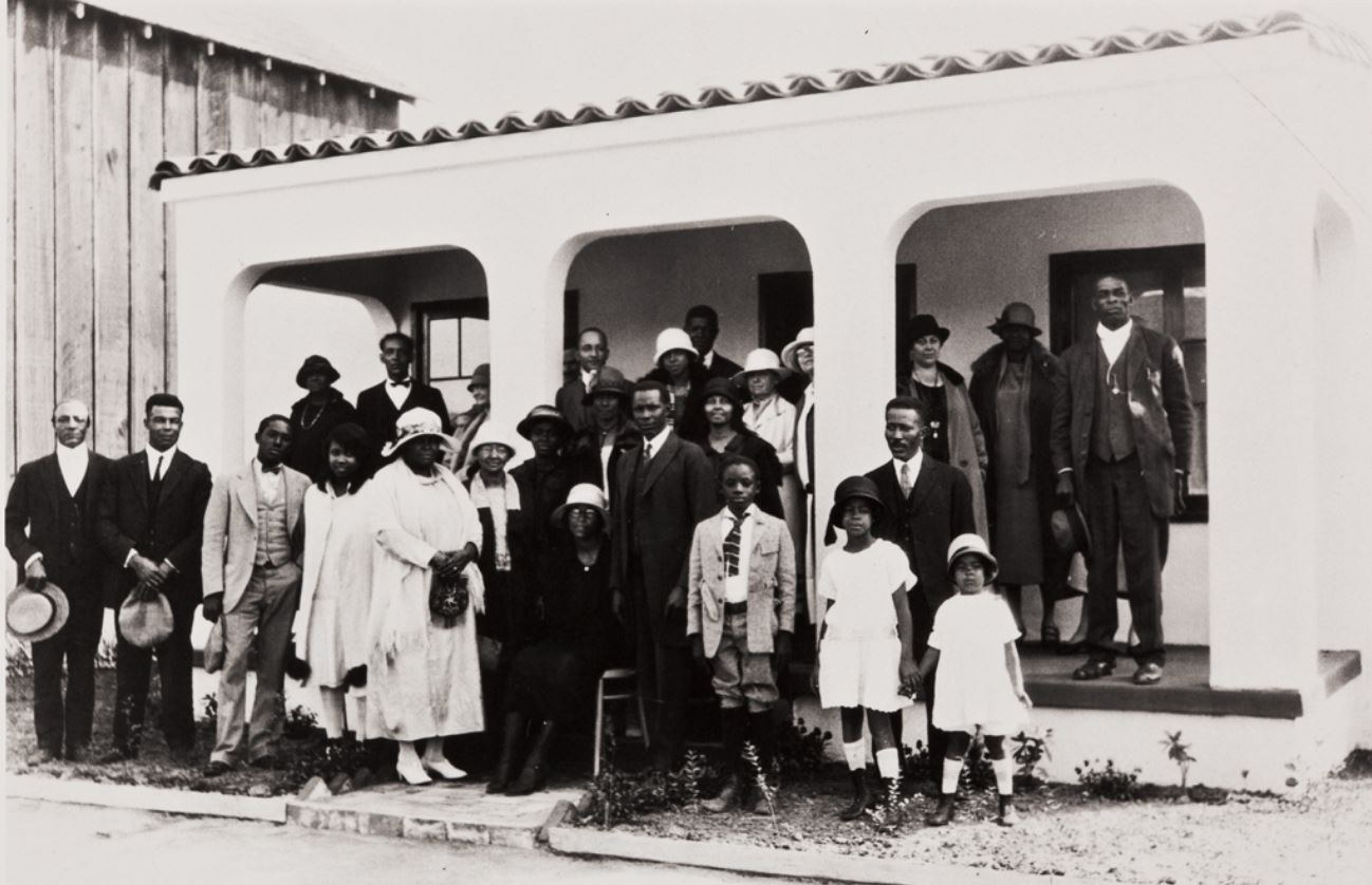 In front of a Santa Barbara home, a group of black leaders gather including civic leader Pearl Chase, third from right on porch, considered to be the mother of the American Riviera look. 1926. Image originally obtained from UCSB Department .JPG
