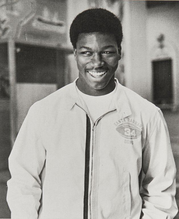 Sam Cunningham smiles and stands with hands in pockets. Printed on his zipped jacket is a football with number _34_ and _Santa Barbara Dons._ Image originally obtained from Santa Barbara High School.JPG
