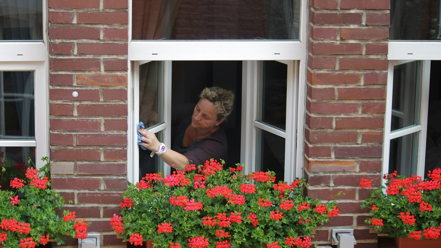 A cleaning lady washing the windows.