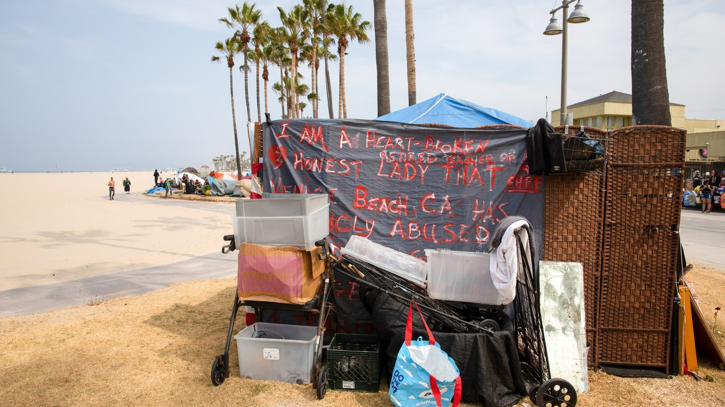 """Along the Venice boardwalk, a tent reads, """"I am a heartbroken retired teacher and chef. Honest lady that Venice Beach, CA, has abused."""" June 29, 2021."""