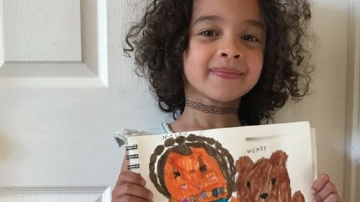 A girl shows off a drawing she learned to do via Wendy MacNaughton's #DrawTogether class.