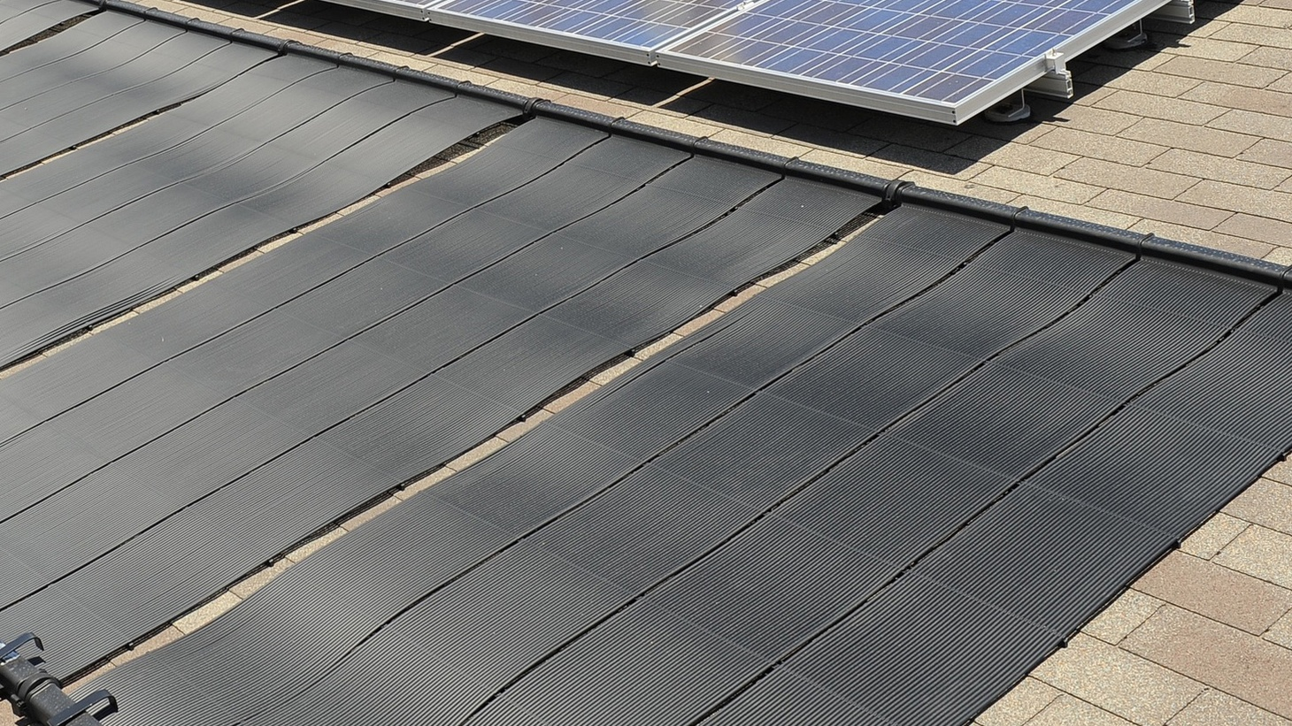Passive solar pool heating on a roof in Florida. Obviously not such a bad place for making use of the technology. While this is a very cool and useful photo for anyone who wants to check out solar pool heating - FYI the solar PV system above is Miami Dade hurricane compliant by having a third rail under the panels.