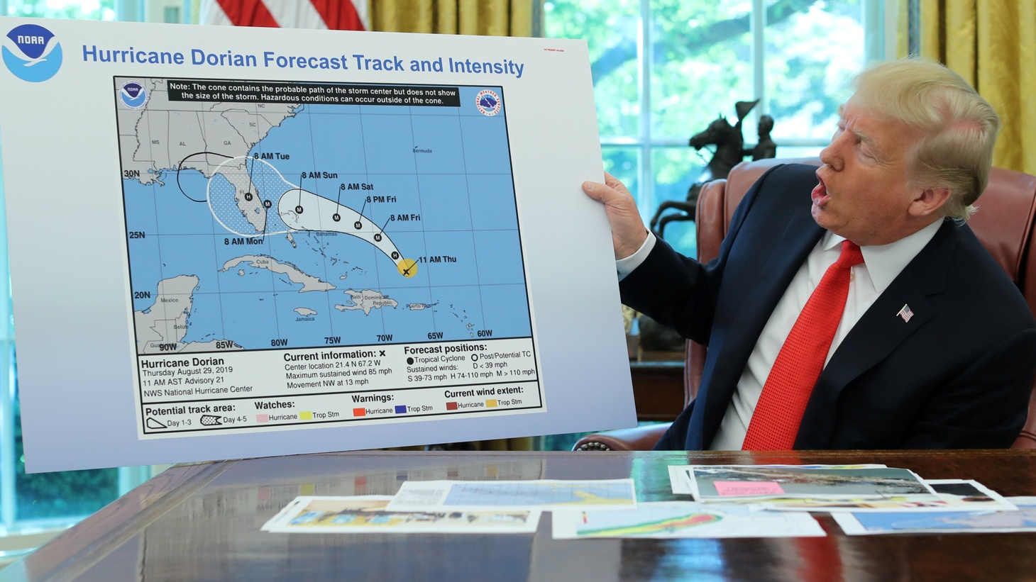 U.S. President Donald Trump holds a chart showing the original projected track of Hurricane Dorian that appears to have been extended with a black line to include parts of the Florida panhandle and of the state of Alabama during a status report meeting on the hurricane in the Oval Office of the White House in Washington, U.S., September 4, 2019.
