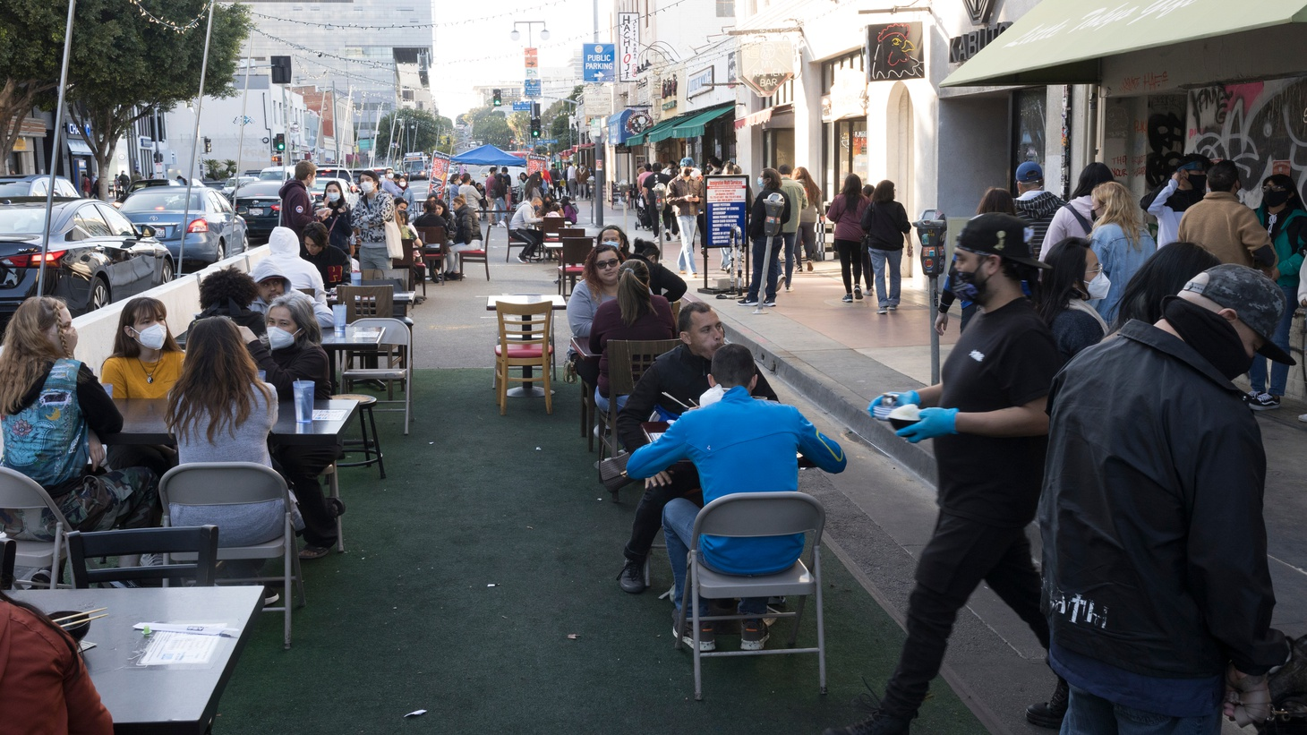 Diners and masked servers are seated outdoors in the street in the Little Tokyo, district of Los Angeles, CA.