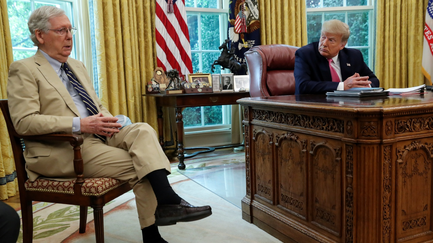 U.S. President Donald Trump listens to Senate Majority Leader Mitch McConnell (R-KY) speak about legislation for additional coronavirus aid in the Oval Office at the White House in Washington, U.S., July 20, 2020.