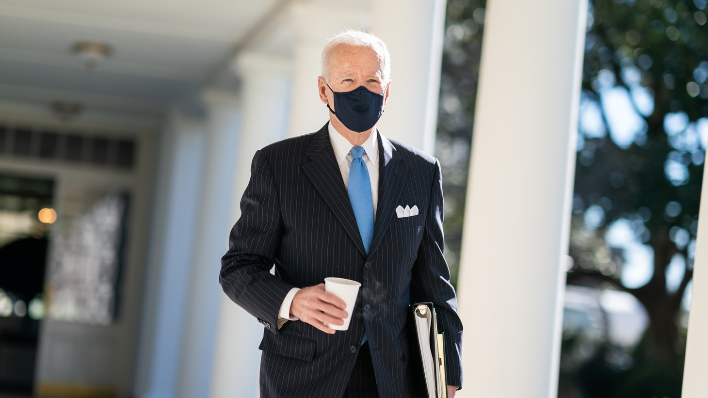 President Joe Biden walks with a cup of coffee, along the Colonnade of the White House to the Oval Office.