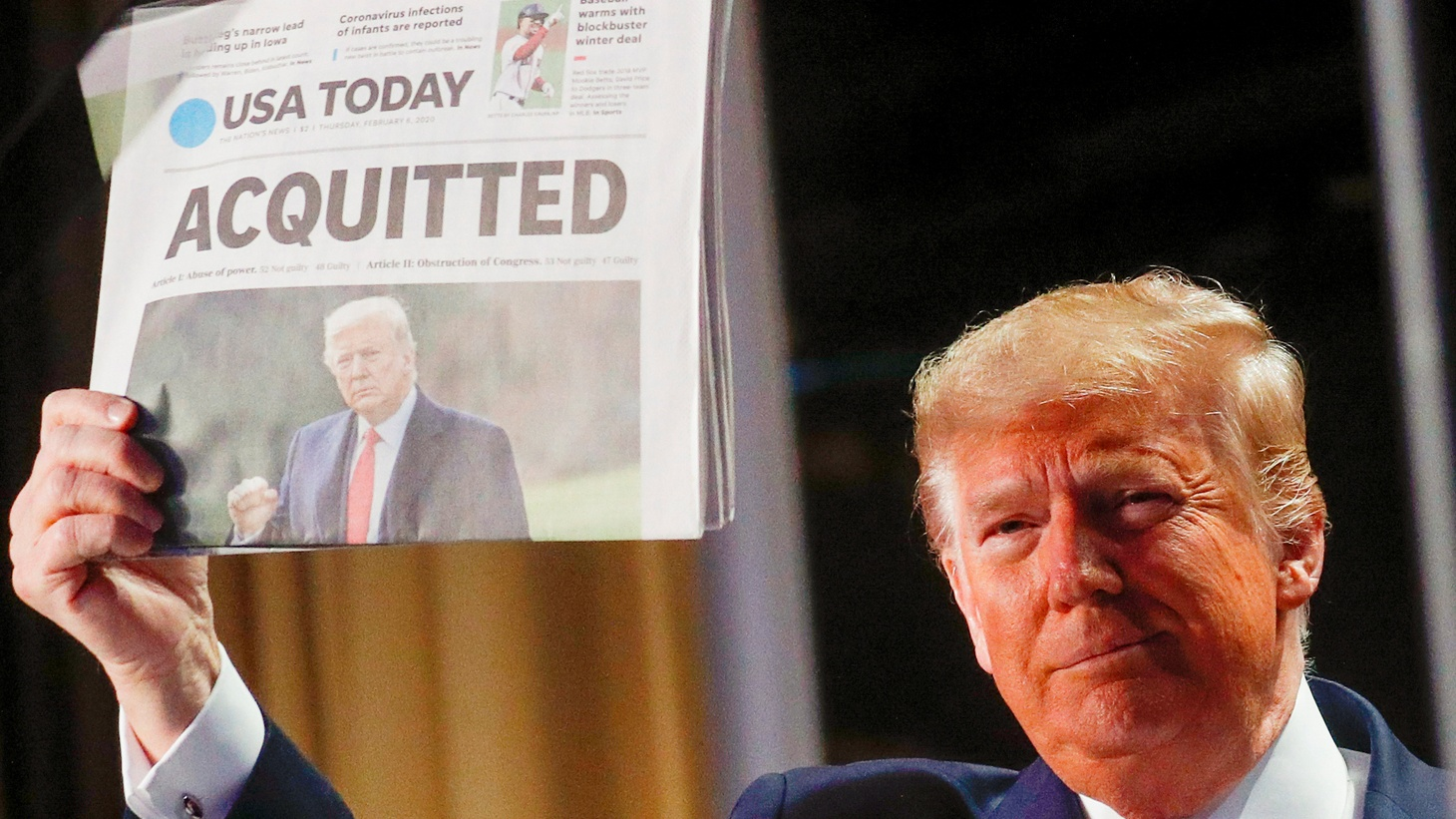 U.S. President Donald Trump holds up a copy of USA Today's front page showing news of his acquitttal in his Senate impeachment trial, as he arrives to address the National Prayer Breakfast in Washington, U.S., February 6, 2020.