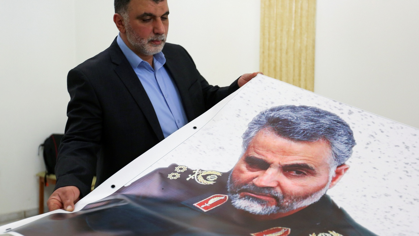 A man holds a banner depicting late Major-General Qassem Soleimani, head of the elite Quds Force, who was killed in a U.S. airstrike Near Baghdad, at the Iranian embassy in Beirut, Lebanon January 3, 2020.