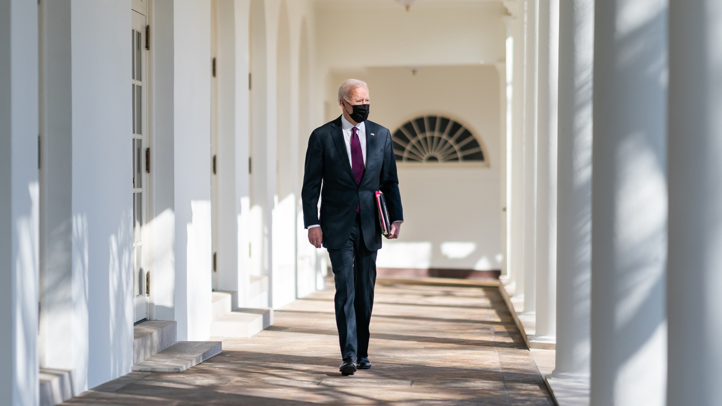 President Joe Biden walks along the Colonnade of the White House to the Oval Office.