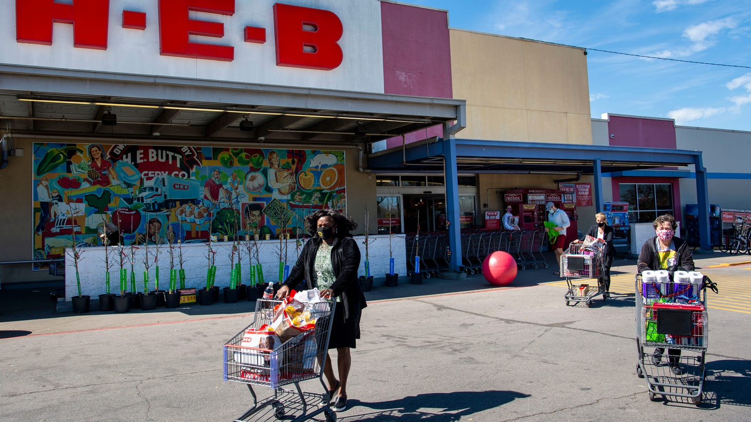 Masked shoppers leave the S. Congress H-E-B on March 3 in Austin, Texas. Texas Gov. Greg Abbott rescinded a mask mandate, but he cautioned Texans to keep wearing them for their own safety.