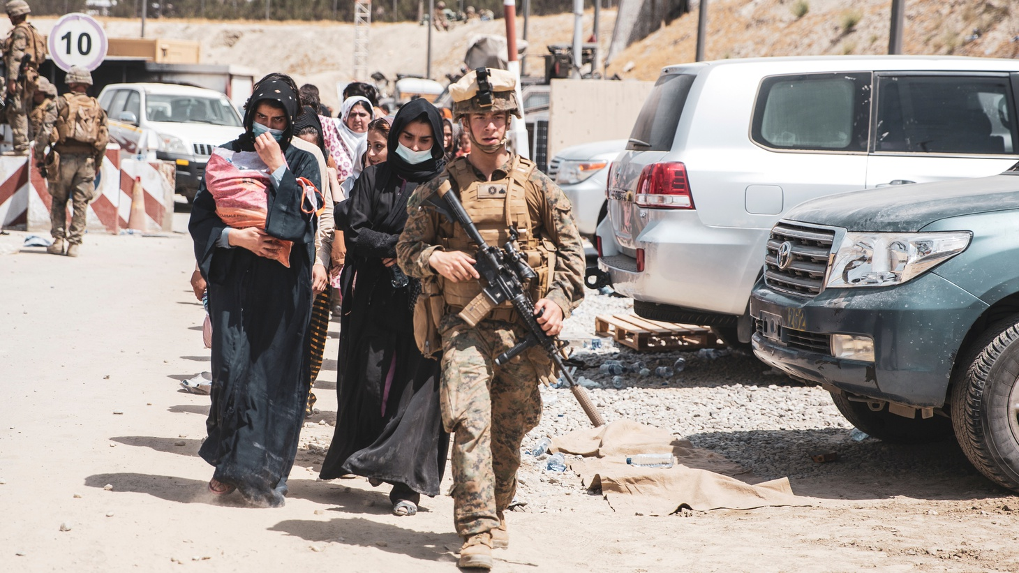 A U.S. Marine escorts evacuees to the Evacuate Control Center at Hamid Karzai International Airport, Kabul, Afghanistan, in this photo taken on August 19, 2021 and released on August 20, 2021.
