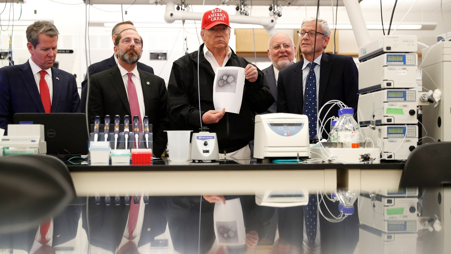 U.S. President Donald Trump displays a photo of the COVID-19 Coronavirus beside Georgia Governor Brian Kemp. HHS Secretary Alex Azar and C.D.C. Associate Director for Laboratory Science and Safety Steve Monroe at the during a tour of the Center for Disease Control in Atlanta, Georgia, U.S., March 6, 2020.