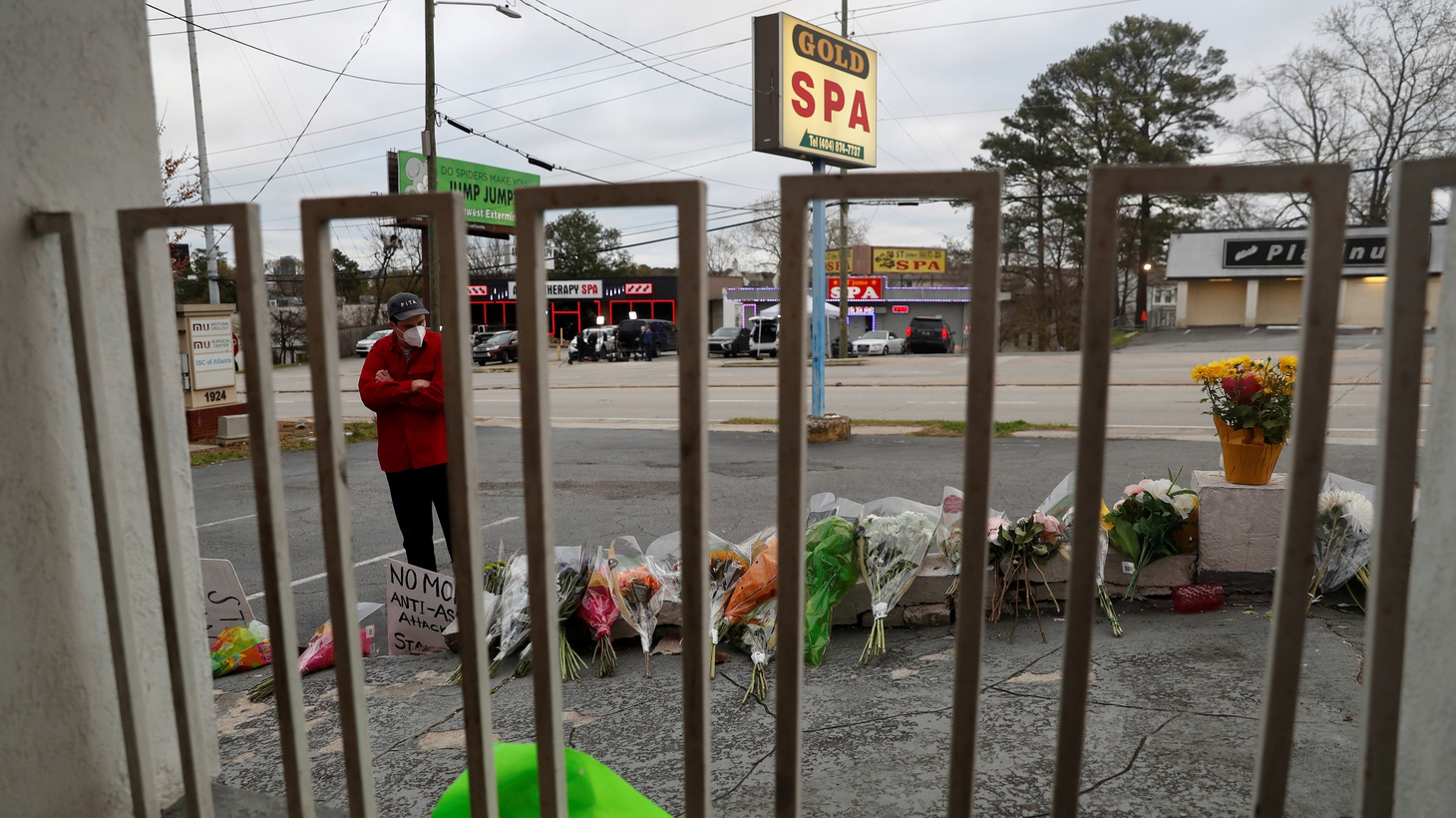 Sasha Hasanbegovic looks down after laying flowers at a makeshift memorial outside the Gold Spa following the deadly shootings in Atlanta, Georgia, U.S. March 19, 2021.