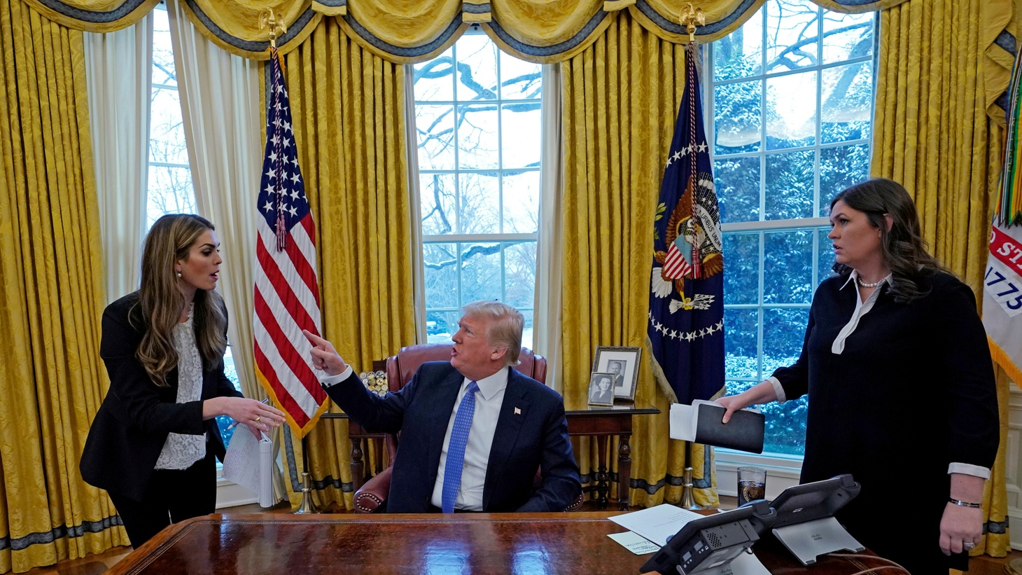 U.S. President Donald Trump confers with White House Communications Director Hope Hicks (L) as White House Press Secretary Sarah Sanders listens during an interview with Reuters at the White House in Washington, U.S., January 17, 2018.