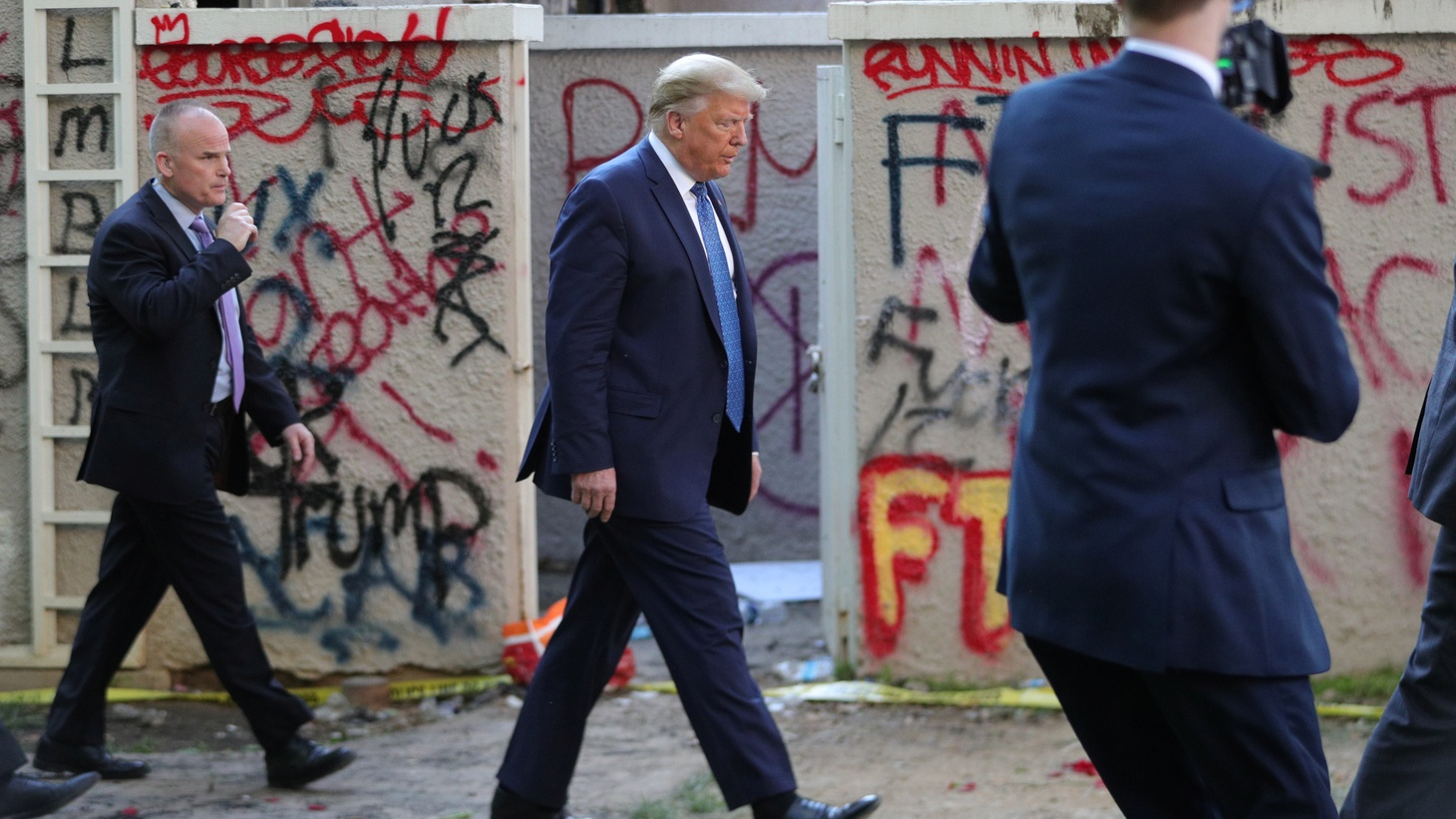 U.S. President Donald Trump walks past a building defaced with graffiti by protestors in Lafayette Park across from the White House after walking to St John's Church for a photo opportunity during ongoing protests over racial inequality in the wake of the death of George Floyd while in Minneapolis police custody, outside the White House in Washington, U.S., June 1, 2020.