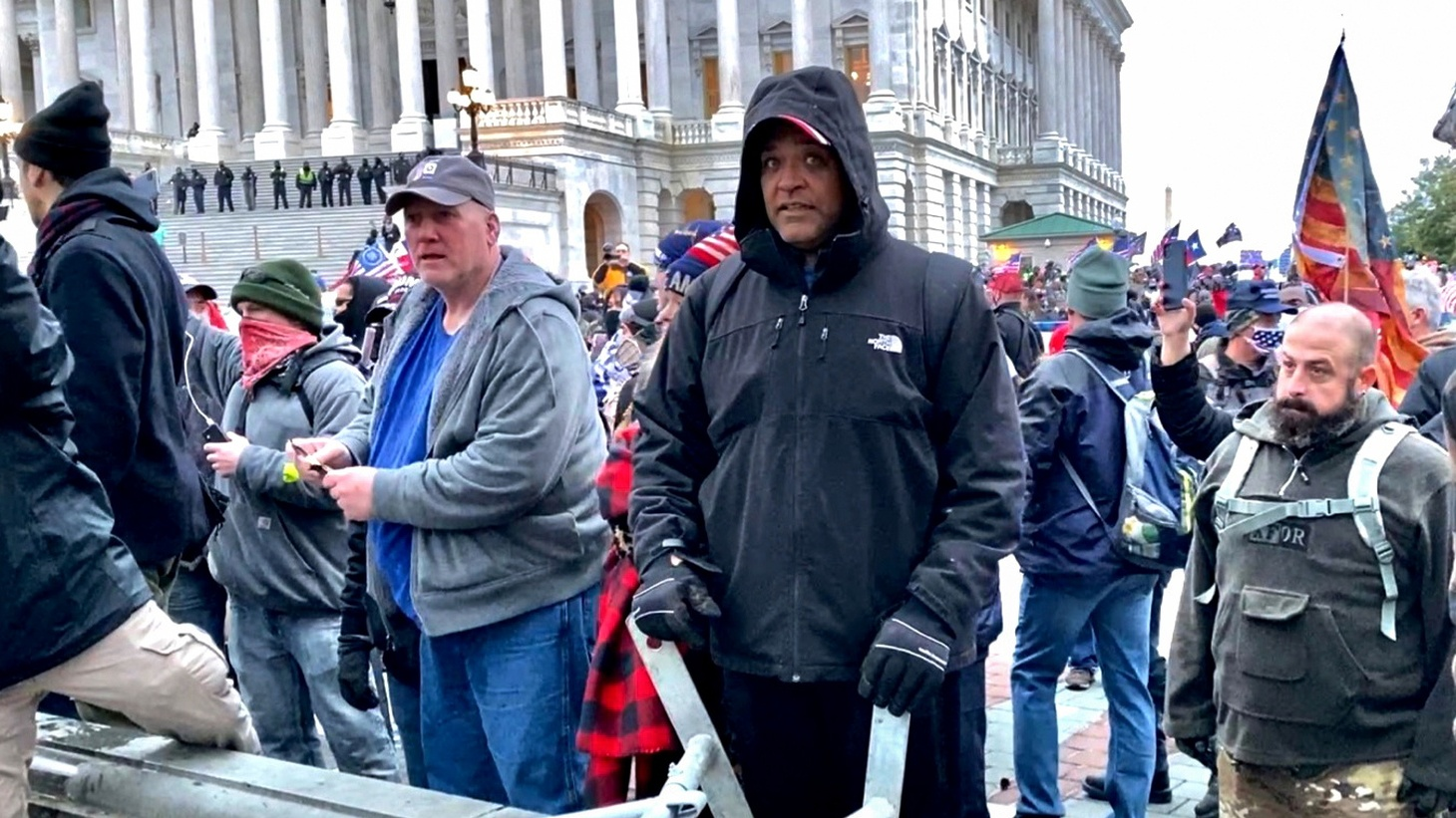 A man (center in black coat) identified by U.S. federal prosecutors as Shane Jason Woods of Auburn, Illinois is seen in a frame grab from video shot during the January 6, 2021 assault on the U.S. Capitol, moments before climbing over a barricade and attacking members of the news media and destroying camera gear. Woods has been charged with assaulting both law enforcement officers and members of the media in an arrest and prosecution announced by U.S. Attorney General Merrick Garland in Washington, U.S. on June 24, 2021.