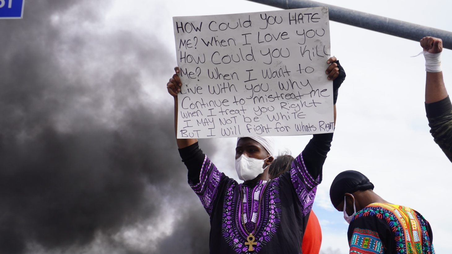 A demonstrator held up a sign while fires burned and protestors congregated in the Fairfax District of Los Angeles May 31.