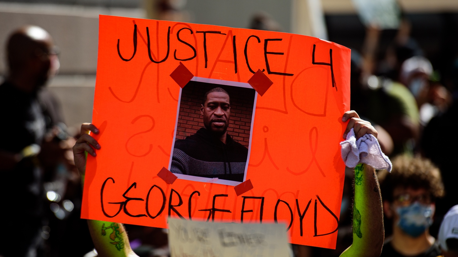Protestor holding a 'Justice for George Floyd' poster.