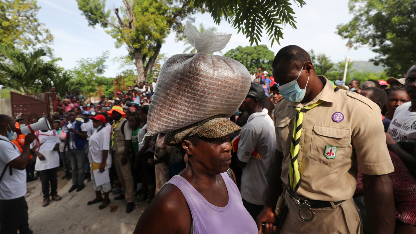 Camp Perrin residents receive food from the World Food Programme (WFP) in Camp Perrin near Les Cayes, after the earthquake that took place on August 14, in Haiti. August 19, 2021.