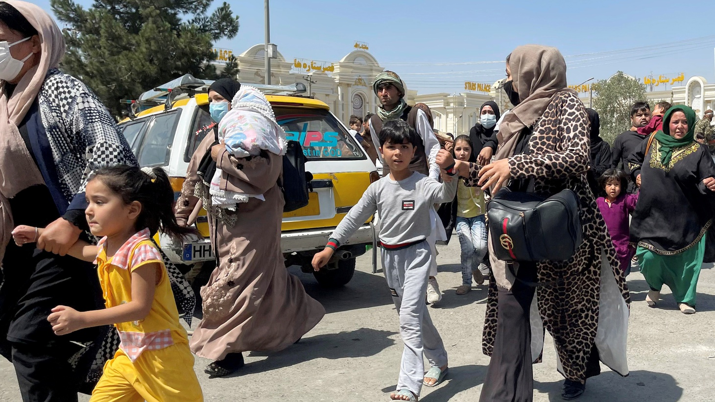 Women with their children try to get inside Hamid Karzai International Airport in Afghanistan, August 16, 2021.