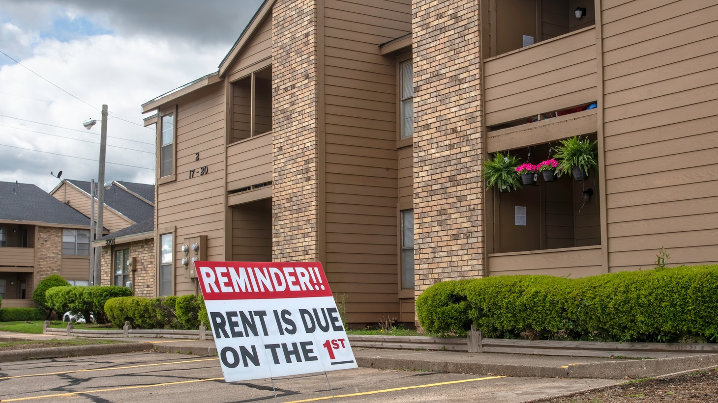 """A sign in the parking lot of an apartment complex reminds renters: """"Rent is due on the 1st."""""""