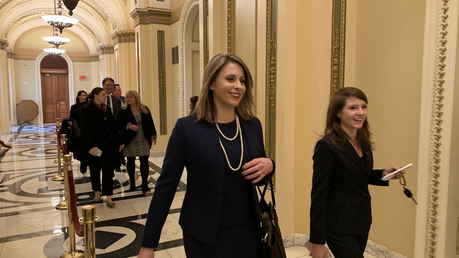 Representative-elect Katie Hill walks through the halls of the Capitol on her way to pick up her member pin, her voting card and her parking pass just before being sworn in as a member of Congress. Photo by Michell Eloy