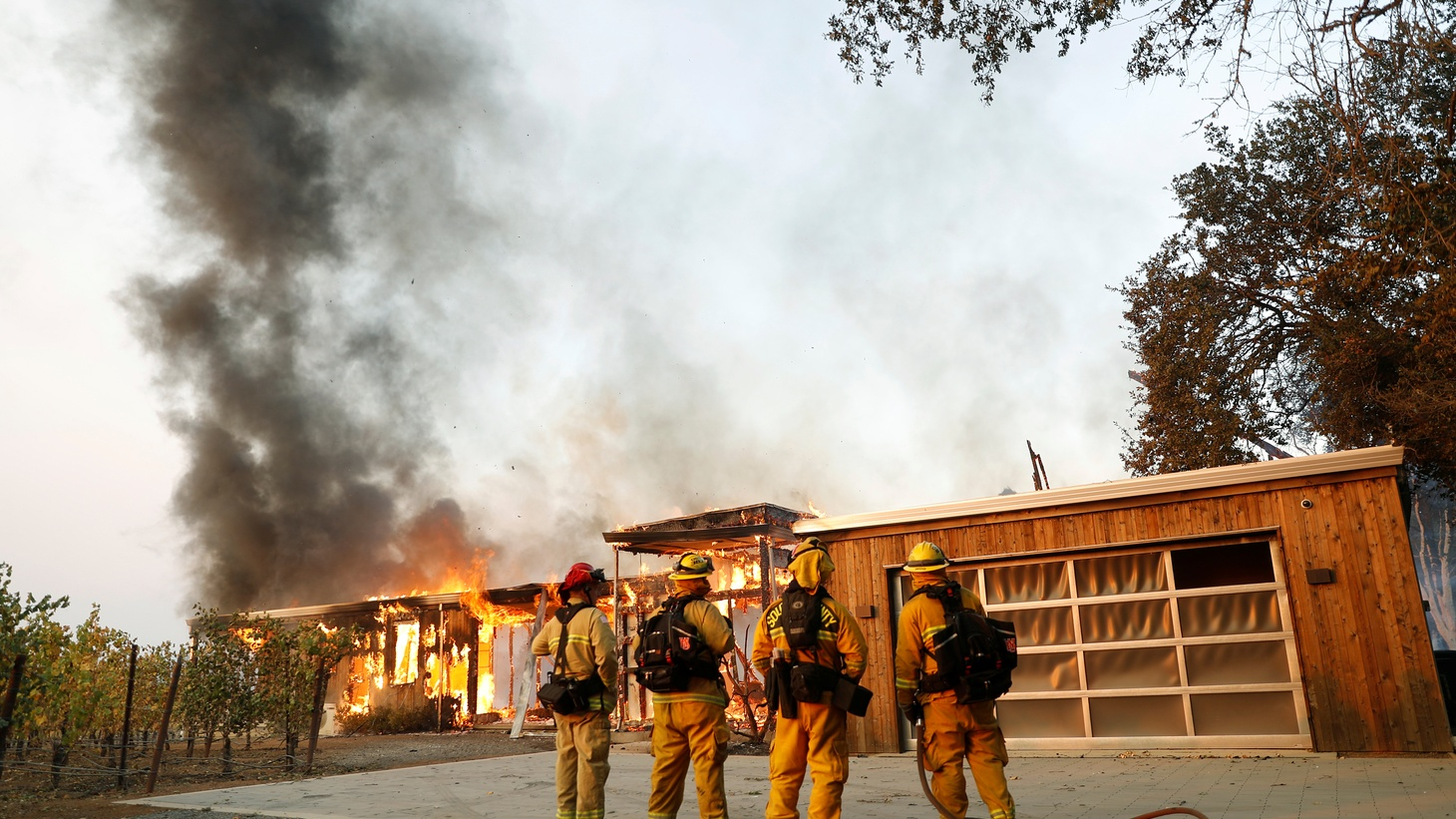 A group of firefighters look on as a house burns during the wind-driven Kincade Fire in Healdsburg, California, U.S. October 27, 2019.