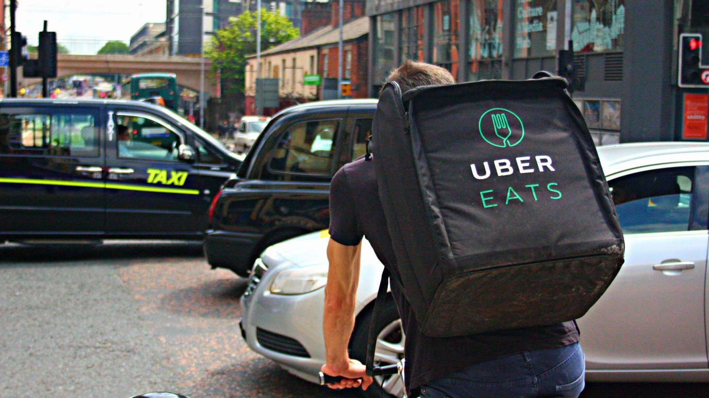 An Uber Eats food delivery driver cycles along a very busy Oxford Road in Manchester. One of a growing number of delivery riders for Uber's food delivery service as demand in Manchester increases.