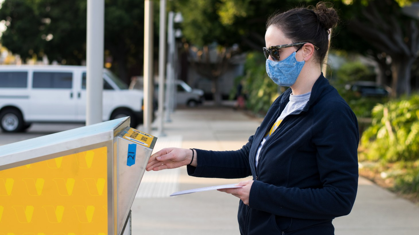 A young woman submits her ballot to a dropoff box in Santa Monica, October 11, 2020.