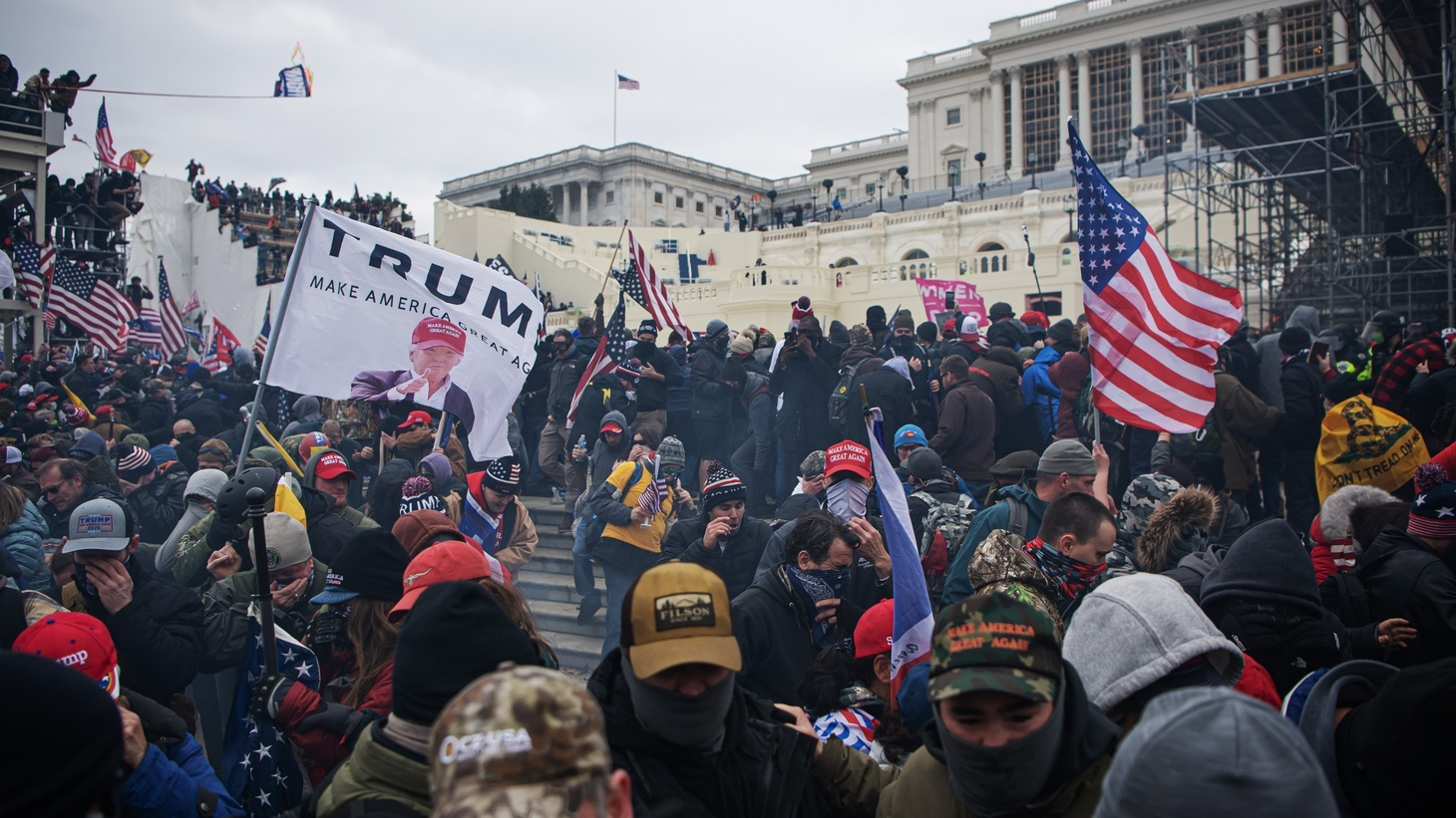 People run away from tear gas as pro-Trump supporters storm the United States Capitol after a March to Save America rally on January 6, 2021 in Washington, DC, USA.