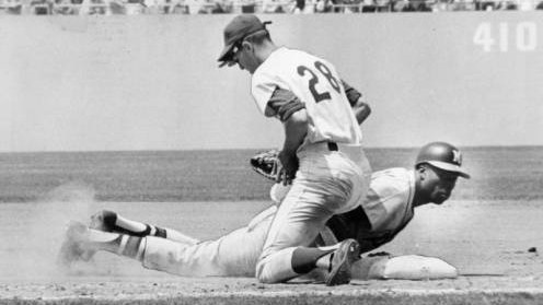 Milwaukee Brave Hank Aaron dives safely back into first base Sunday during attempted pickoff by Dodger pitcher Howie Reed. Applying tag is LA first baseman Wes Parker. Action came in first game of a double header in which the Braves beat the Dodgers twice by identical scores of 5-1. June 15, 1964.
