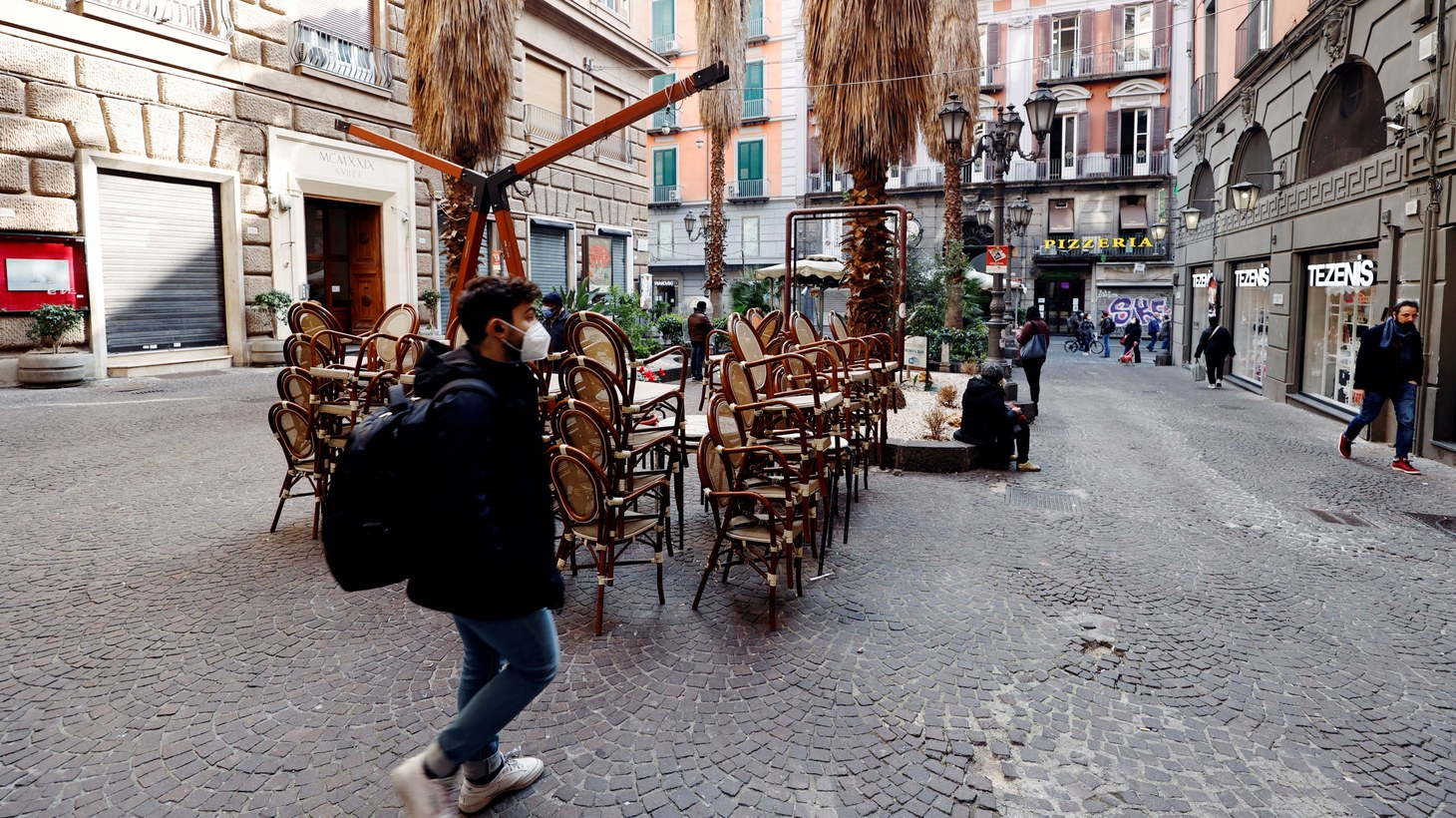 """People walk past empty chairs after the region of Campania became a """"red zone,"""" increasing restrictions due to a rise in the coronavirus disease (COVID-19) infections, in Naples, Italy, March 8, 2021."""