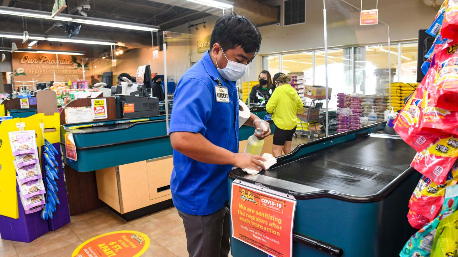 Workers sanitize conveyor belts after every single transaction to maintain cleanliness for shoppers at the Pay-Less Supermarket store in Dededo. Aug. 19, 2020.