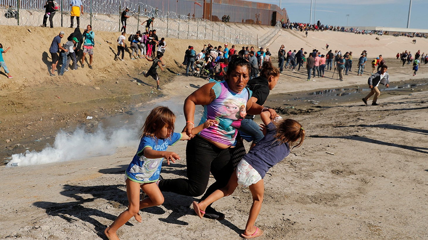 Maria Lila Meza Castro (C), a 39-year-old migrant woman from Honduras, part of a caravan of thousands from Central America trying to reach the United States, runs away from tear gas with her five-year-old twin daughters Saira Nalleli Mejia Meza (L) and Cheili Nalleli Mejia Meza (R) in front of the border wall between the U.S. and Mexico, in Tijuana, Mexico November 25, 2018.
